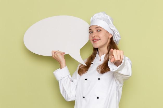 緑の壁に大きな白い看板を保持している白いクックスーツの女性料理人の正面図 無料写真