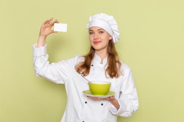 Вид спереди повара в белом костюме повара, держащего карточку и тарелку на зеленой стене Бесплатные Фотографии