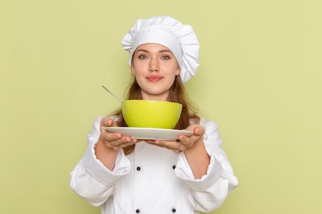 緑のプレートを保持し、緑の壁に笑みを浮かべて白いクックスーツの女性料理人の正面図 無料写真
