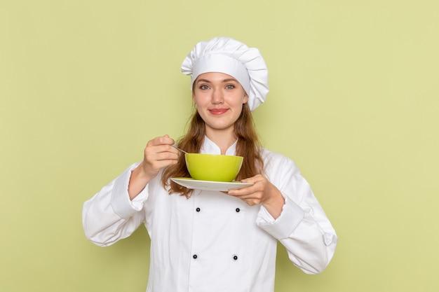 緑の壁に緑のプレートを保持している白いクックスーツの女性料理人の正面図 無料写真