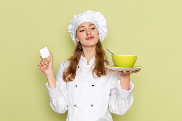 Вид спереди повара в белом костюме повара, держащего зеленую тарелку на зеленой стене Бесплатные Фотографии