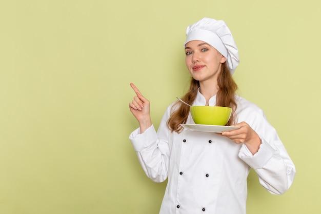 薄緑色の壁に緑のプレートを保持している白いクックスーツの女性料理人の正面図 無料写真