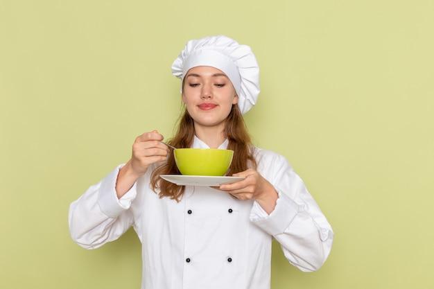 緑の机の上の皿と緑のプレートを保持している白いクックスーツの女性料理人の正面図キッチン料理料理料理食事女性 無料写真