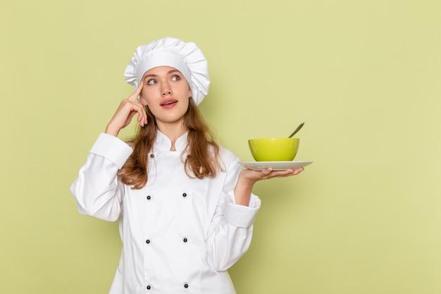 緑の壁に皿と緑のプレートを保持している白いクックスーツの女性料理人の正面図 無料写真
