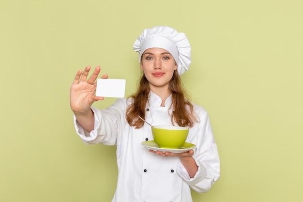 緑の壁にプレートとカードを保持している白いクックスーツの女性料理人の正面図 無料写真