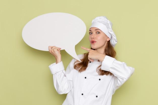 緑の壁に白い看板を保持している白いクックスーツの女性料理人の正面図 無料写真