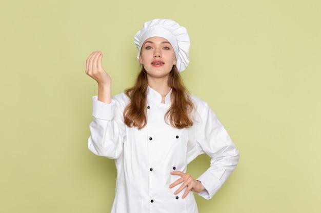 緑の壁にポーズをとって白いクックスーツの女性料理人の正面図 無料写真