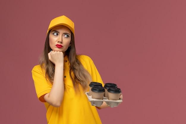 Вид спереди курьера-женщины в желтой униформе и кепке, держащего коричневые кофейные чашки и глубоко размышляющего о розовой стене Бесплатные Фотографии