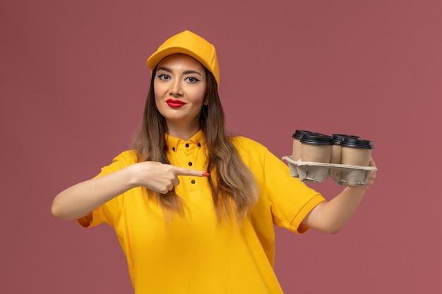 Вид спереди курьера-женщины в желтой форме и кепке, держащего коричневые кофейные чашки на розовой стене Бесплатные Фотографии