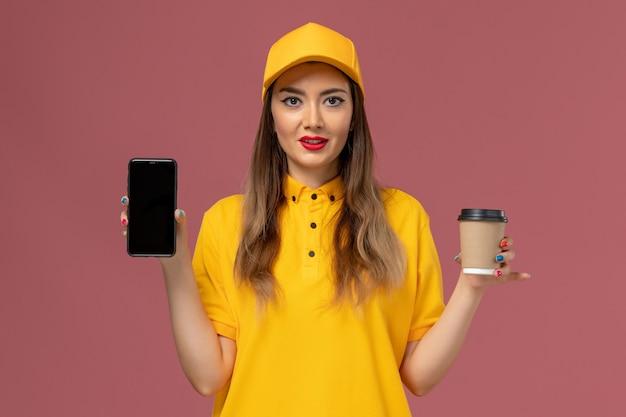 Вид спереди курьера в желтой форме и кепке, держащего чашку кофе и телефон на розовой стене Бесплатные Фотографии