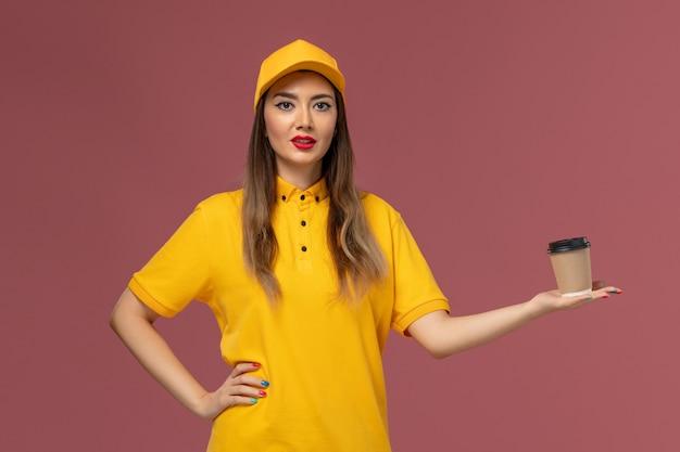 Вид спереди курьера-женщины в желтой униформе и кепке, держащего чашку кофе на розовой стене Бесплатные Фотографии
