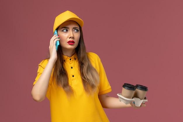 Вид спереди курьера-женщины в желтой форме и кепке, держащего кофейные чашки с доставкой, разговаривает по телефону на розовой стене Бесплатные Фотографии