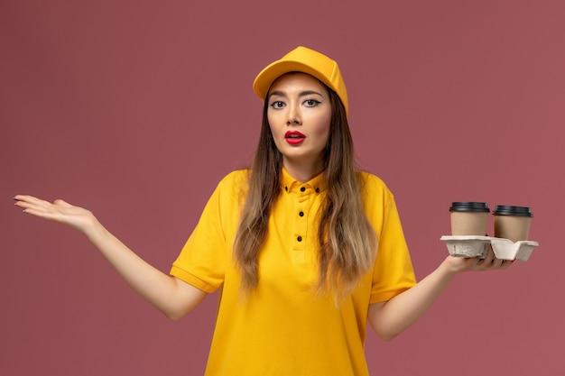 Вид спереди курьера-женщины в желтой форме и кепке, держащего кофейные чашки на розовой стене Бесплатные Фотографии