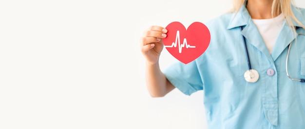 ハートビートと紙のハートを保持している聴診器で女医の正面図 Premium写真