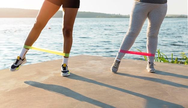 Вид спереди подруг, вместе тренирующихся на берегу озера Бесплатные Фотографии