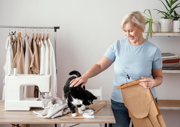 猫とスタジオで女性の仕立て屋の正面図 無料写真