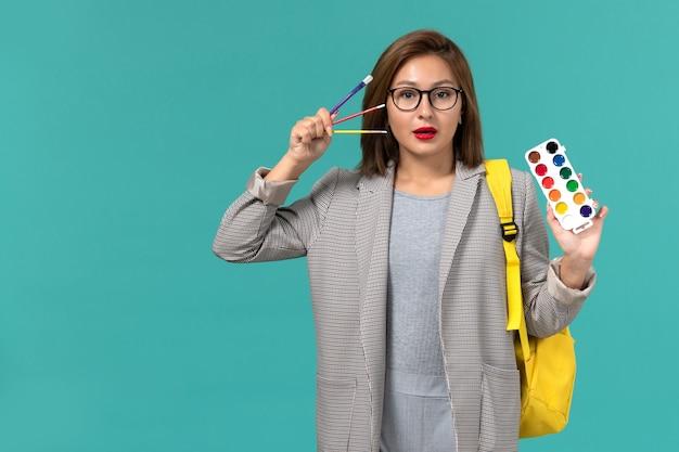 Вид спереди студентки в серой куртке в желтом рюкзаке с красками на синей стене Бесплатные Фотографии