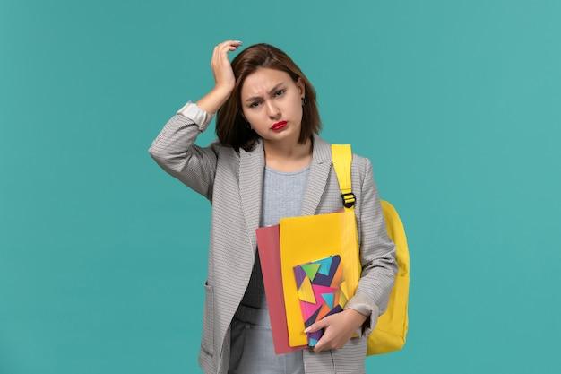 파란색 벽에 두통이있는 파일 및 카피 북을 들고 노란색 배낭을 착용하는 회색 재킷에 여성 학생의 전면보기 무료 사진