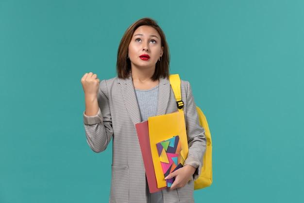 青い壁にファイルとコピーブックを保持している黄色のバックパックを身に着けている灰色のジャケットの女子学生の正面図 無料写真