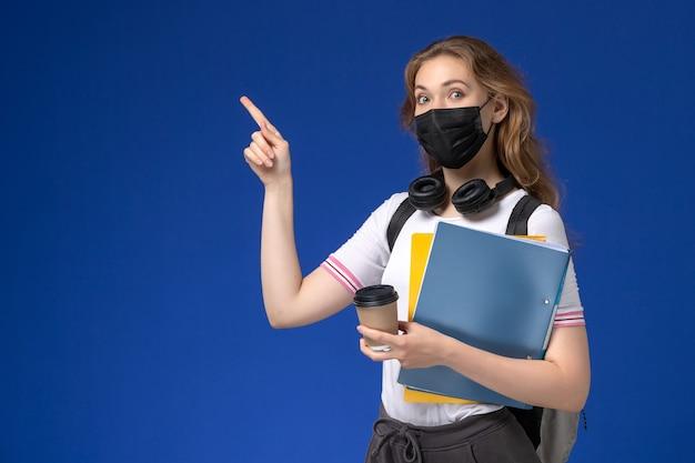 Вид спереди студентки в белой рубашке, носящей рюкзак, черная стерильная маска, держащая кофе и файлы на синей стене Бесплатные Фотографии