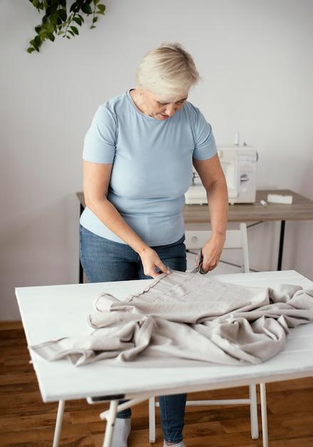 スタジオカッティングファブリックの女性仕立て屋の正面図 Premium写真