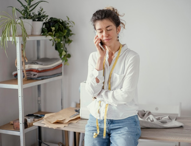 電話で話している女性の仕立て屋の正面図 無料写真
