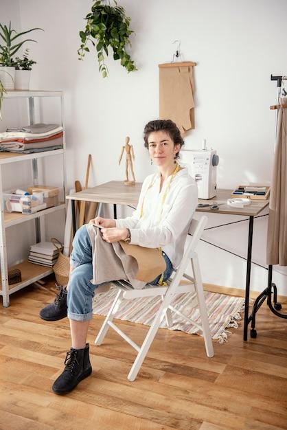 スタジオで働く女性の仕立て屋の正面図 無料写真