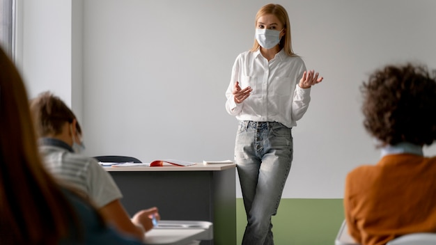 Вид спереди учительницы с медицинской маской, преподающей в классе Premium Фотографии
