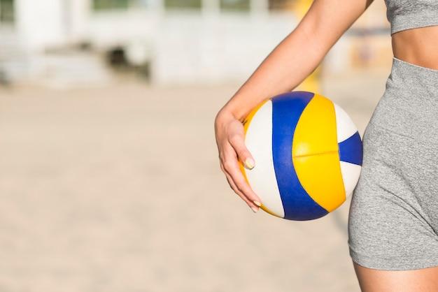 コピースペースでボールを保持しているビーチで女子バレーボール選手の正面図 無料写真