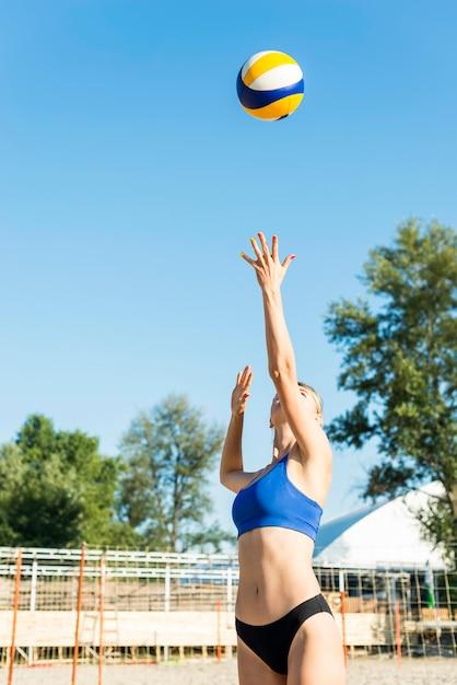 ビーチのサービングボールの女子バレーボール選手の正面図 無料写真