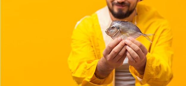 コピースペースでキャッチを保持している漁師の正面図 無料写真