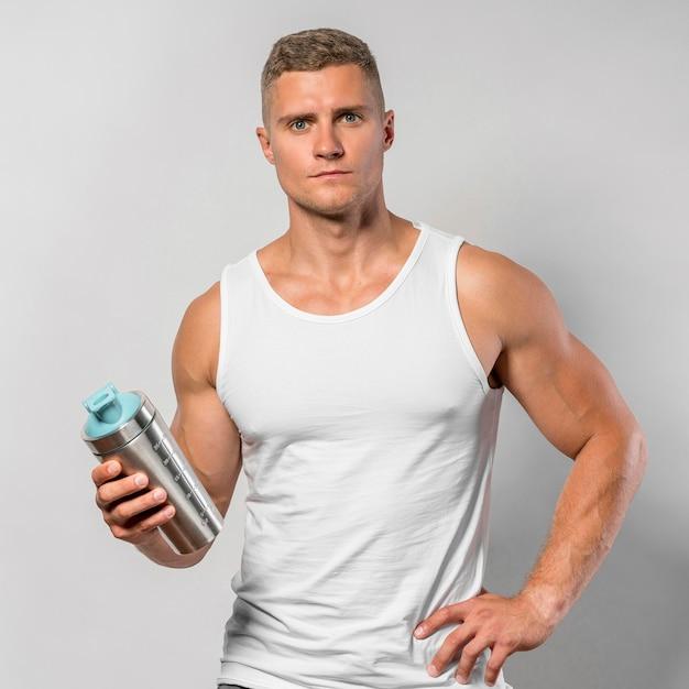 Вид спереди здорового человека, позирующего, держа бутылку с водой Бесплатные Фотографии