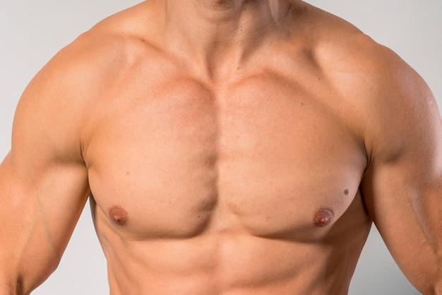 ペーチを示すフィット上半身裸の男の正面図 無料写真