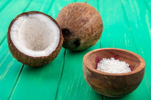 緑の表面に木製のボウルにココナッツパウダーと新鮮なココナッツの正面図 無料写真