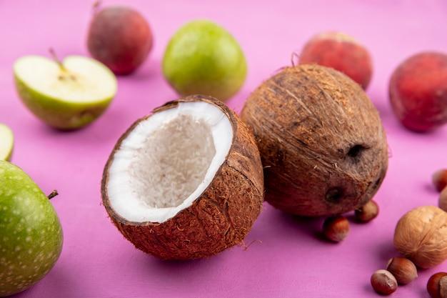 ピンクの表面に青リンゴ桃と新鮮なココナッツの正面図 無料写真