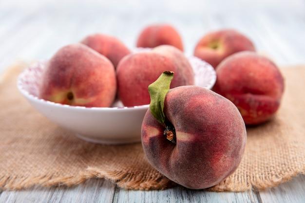 白い表面に分離された桃と白いボウルに新鮮なジューシーでおいしい桃の正面図 無料写真