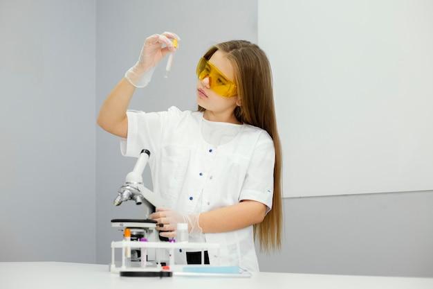 현미경 및 테스트 튜브와 여자 과학자의 전면보기 무료 사진