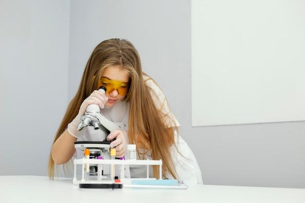 안전 안경 및 현미경으로 여자 과학자의 전면보기 무료 사진