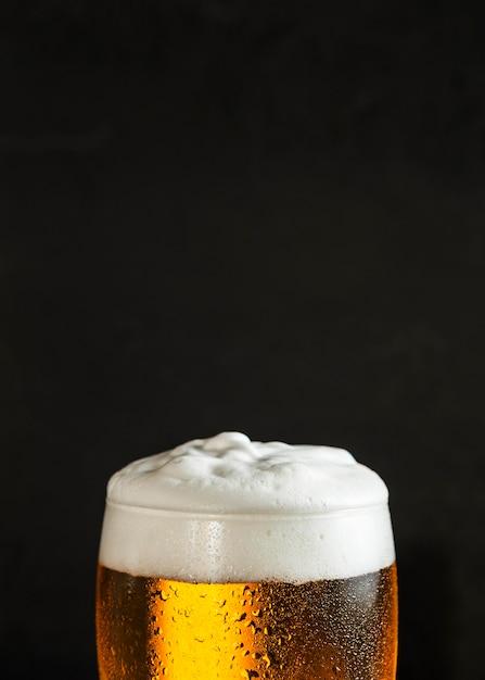 泡とコピースペースとビールのガラスの正面図 Premium写真