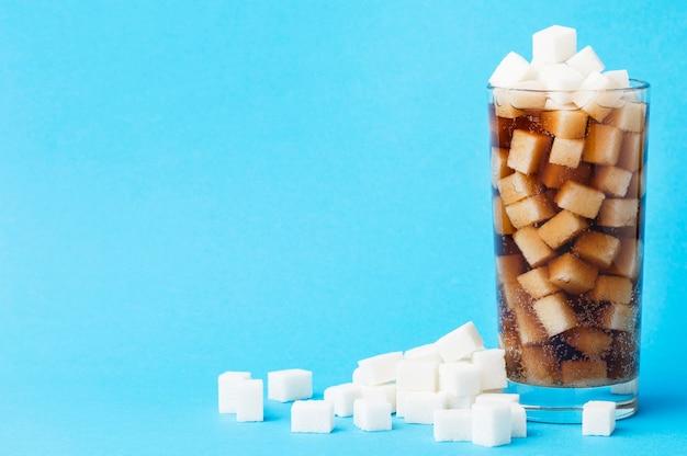 Вид спереди стакана безалкогольного напитка с кубиками сахара и копией пространства Бесплатные Фотографии