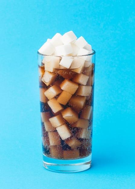 Вид спереди стекла с безалкогольным напитком и кубиками сахара Бесплатные Фотографии