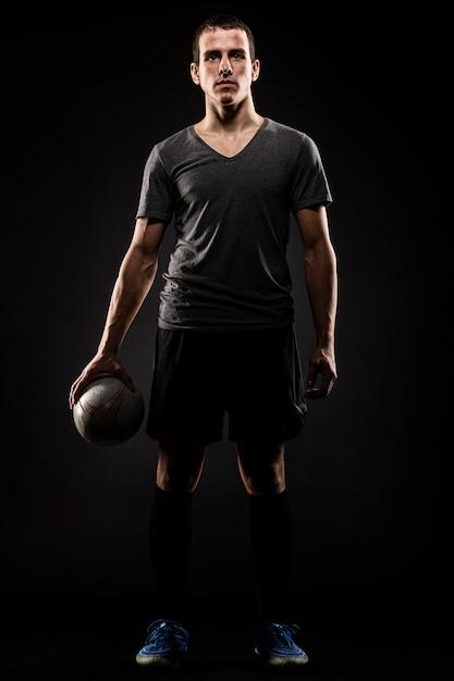 Вид спереди красивого мужского игрока в регби, держащего мяч Premium Фотографии