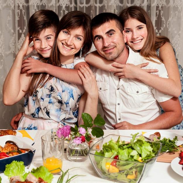 Вид спереди счастливой семьи позирует за обеденным столом Бесплатные Фотографии