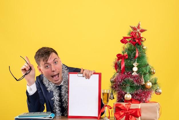 クリスマスツリーの近くのテーブルに座って、黄色で提示する幸せな男の正面図 無料写真