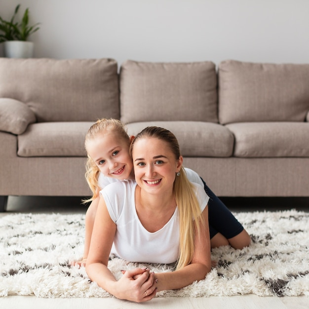 Вид спереди счастливой матери и дочери, позирует дома Бесплатные Фотографии