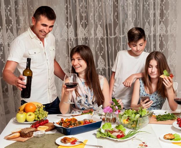 夕食の席で幸せな親と子の正面図 無料写真