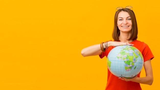 Вид спереди счастливой женщины, держащей глобус с копией пространства Бесплатные Фотографии