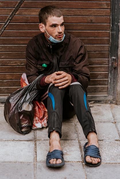 屋外でビニール袋を持つホームレスの男性の正面図 Premium写真