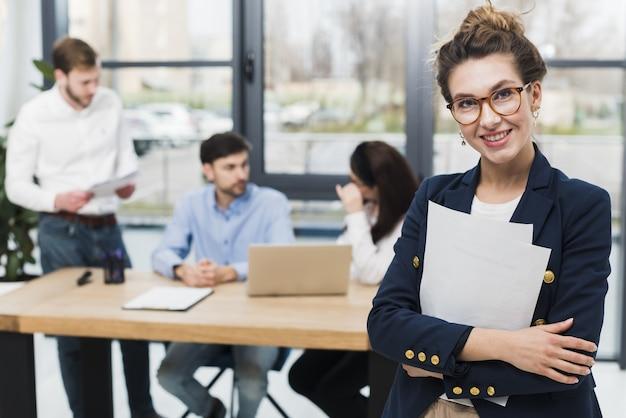 Вид спереди человеческих ресурсов женщина позирует в офисе Бесплатные Фотографии