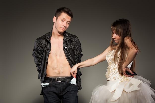 男性のズボンの空のポケットを保持している女性の正面図。紳士をがっかり見つめている女の子が無邪気な表情で見下ろしている男。灰色のスタジオの背景に分離。お金がないという概念。 Premium写真